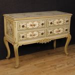 Italian lacquered, golden and painted chest of drawers with floral decorations